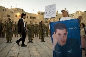In this Aug. 12, 2009 file photo, an Israeli activist held a banner of Israeli soldier Sgt. Gilad Schalit at the Western Wall in Jerusalem.