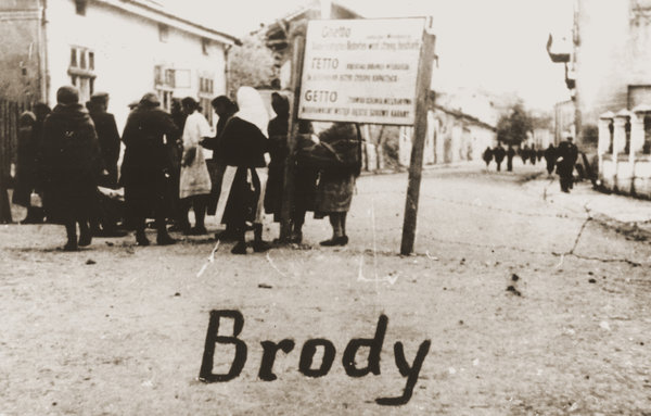 A group of Jewish women at the entrance to the Brody Ghetto in Eastern Galicia, 1942. The sign is written in German, Ukrainian and Polish. (United States Holocaust Memorial Museum / Collection of Eugenia Hochberg Lanceter)