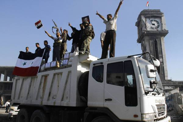 Forces loyal to the Syrian army celebrate as they drive through the main square of Qusair after helping President Bashar Assad's soldiers retake control of the area this month. (AFP/Getty Images / June 5, 2013)