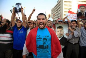 KHALIL HAMRA/AP Supporters of Egypt's ousted President Mohammed Morsi hold aloft  pictures of him as they protest in front of a Republican Guard headquarters in Cairo on Saturday. Arabic writing on the protester's blue shirt reads 'Free revolutionaries will continue the way'.