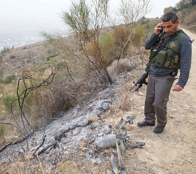 An Israeli regional security officer stands looks over the rocket's debris. Relations between the two countries had been relatively peaceful until Dec 29 attacks.