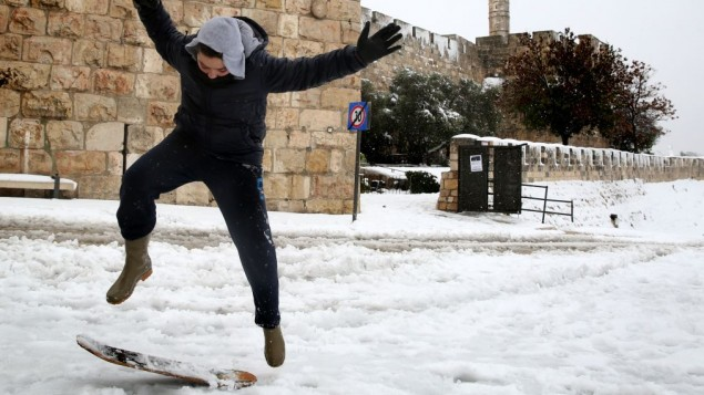 A young boy snowboards at Jaffa Gate outside the Old City of Jerusalem, on the third day of the major snowstorm that hit the capital, Saturday, December 14, 2013. (photo credit: Hadas Parush/Flash 90)