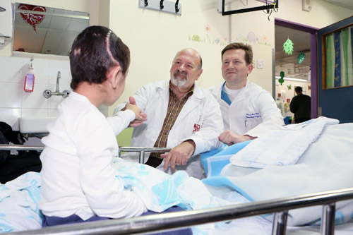 """K"" with two of Rambam's senior neurosurgeons, Dr. Joseph Juilburd (left) and Dr. Sergey Abeshaus (right). (Photo: Pioter Fliter, RHCC)"