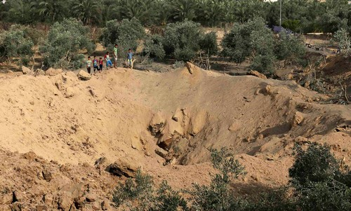 Palestinian boys look at a crater which police said was caused by an Israeli air strike in the central Gaza Strip July 7, 2014. // Reuters