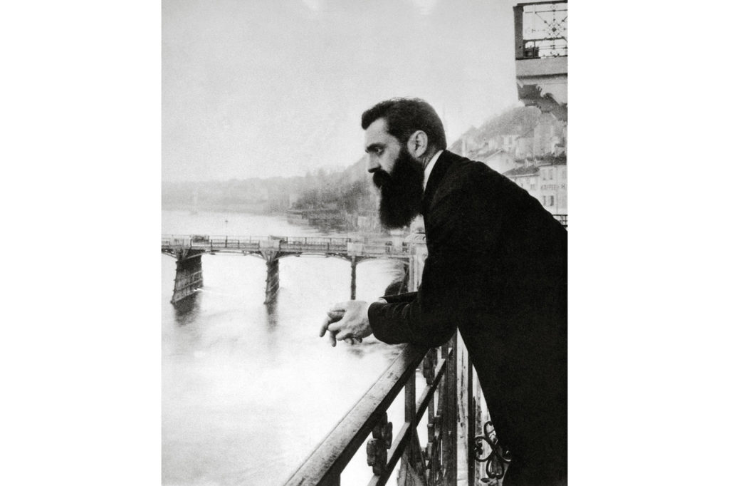 The founder of Zionism, Theodor Herzl, looks out over the Rhine River from the balcony of the hotel in Basel, Switzerland, where he stayed during the First Zionist Congress in 1897. Israeli historian and former diplomat Michael B. Oren defines Zionism as 'the belief that the Jewish people should have their own sovereign state in the Land of Israel.'