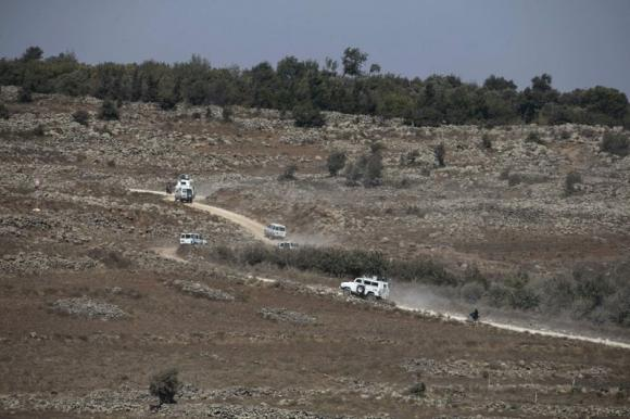 U.N. vehicles drive in Syria near the border fence with the Israeli-occupied Golan Heights September 2, 2014. Credit: Reuters/Baz Ratner