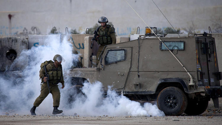 Israeli soldiers run from tear gas during clashes outside the Ofer military prison near the West Bank city of Ramallah on Nov. 18. (Majdi Mohammed / Associated Press)