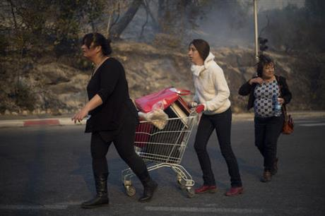People carry their belongings inside a supermarket cart as they evacuate from wildfires in Haifa, Israel, Thursday, Nov. 24, 2016. A raging wildfire ripped through parts of Israel's third-largest city on Thursday, forcing tens of thousands of people to evacuate their homes and prompting a rare call-up of hundreds of military reservists to join overstretched police and firefighters. Spreading quickly due to dry, windy weather, the fire quickly spread through Haifa's northern neighborhoods. While there were no serious injuries, several dozen people were hospitalized for smoke inhalation. (AP Photo/Ariel Schalit)