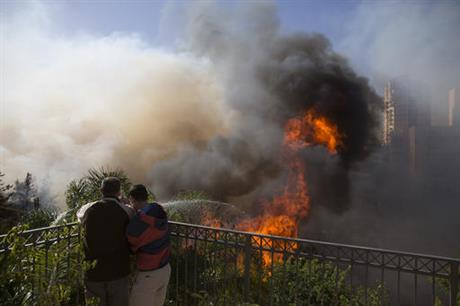 Men hose down wildfires in Haifa, Israel, Thursday, Nov. 24, 2016. Israeli police have arrested four Palestinians in connection with one of several large fires that damaged homes and prompted the evacuation of thousands of people in the past few days. Police are investigating the causes, including possible arson. Windy and hot weather have helped fan the flames. The blazes started three days ago near Jerusalem and in the north. Hundreds of homes were damaged. Russia, Italy and other countries are assisting the Israeli firefighters. (AP Photo/Ariel Schalit)