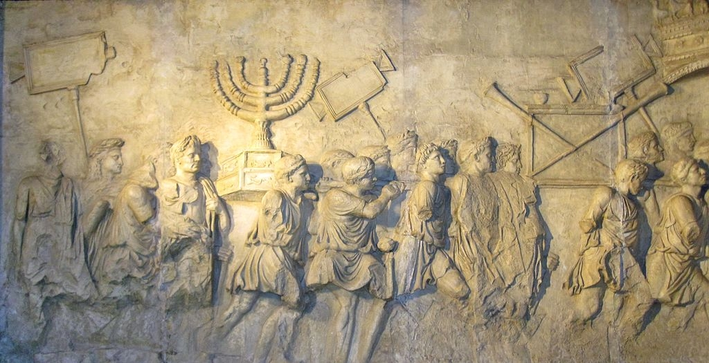 In Rome, any present-day tourist can behold, on the ancient Arch of Titus, the engraved likeness of the Jewish candelabra (Menorah), which the Romans brought back from Jerusalem after ransacking the Jewish Temple. Pictured: Photo of a panel copy from the Arch of Titus, displayed in the Beth Hatefutsoth museum in Israel. (Image source: Wikimedia Commons/Sodabottle)
